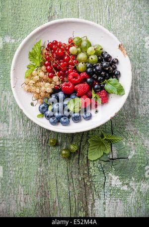 Mix di frutti di bosco freschi con foglie in ceramica vintage scolapasta sul verde rustico sfondo di legno Foto Stock