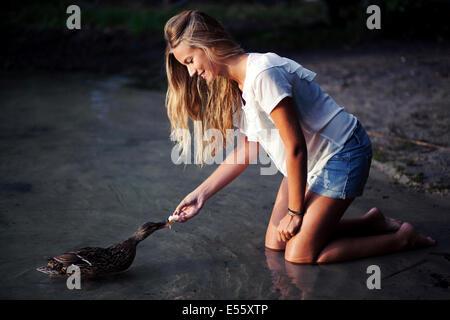 Giovane donna alimentando un anatra Foto Stock