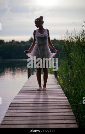 Giovane donna in abito bianco in piedi su una passerella sul lago Foto Stock