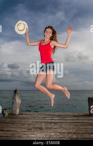 Giovane bella donna che si tuffa in felicità alla fine del molo all'oceano Foto Stock