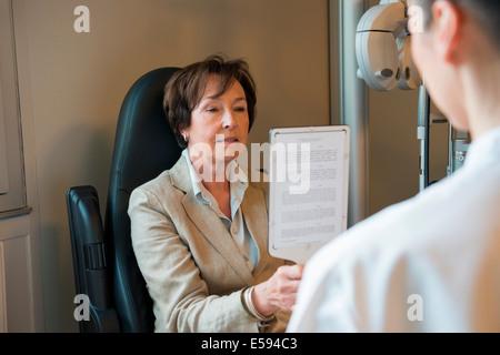Paziente di sesso femminile avente un esame degli occhi in una clinica all'ottico optometrista Foto Stock