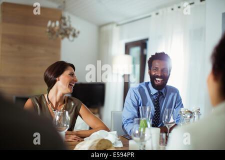 Gli amici di ridere a cena Foto Stock
