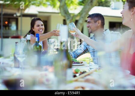 Amici tostare ogni altro a cena all'aperto Foto Stock