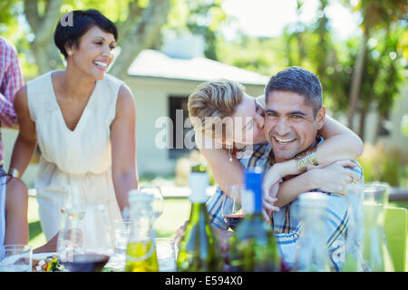 Giovane kissing a tavola all'aperto Foto Stock