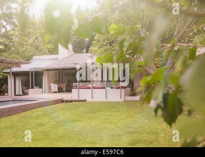 La piscina e il prato nel cortile di casa moderna Foto Stock