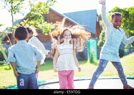 I bambini di saltare sul trampolino all'aperto Foto Stock