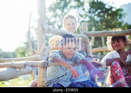 L insegnante e gli studenti giocando sulla struttura di gioco Foto Stock