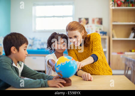 Studenti e insegnanti globo di esame in aula Foto Stock