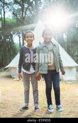 Ragazze sorridenti da teepee al campeggio Foto Stock