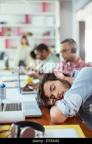 Uomo dorme da scrivania in ufficio Foto Stock
