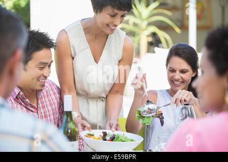 Donna che serve gli amici a tavola all'aperto Foto Stock