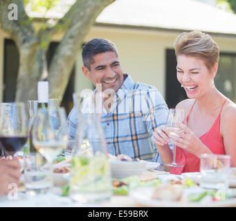 Paio di ridere a tavola all'aperto Foto Stock