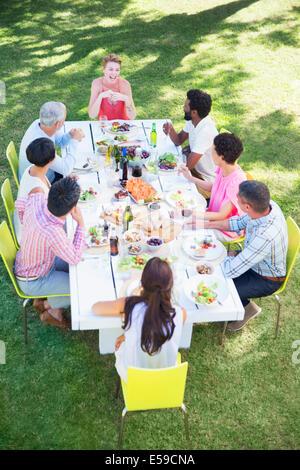 Gli amici di mangiare insieme a tavola all'aperto Foto Stock