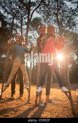 Gli insegnanti aiutano gli studenti a piedi su palafitte all'aperto Foto Stock