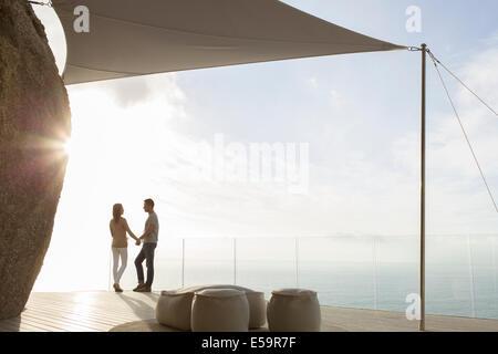 Matura in piedi sul balcone moderno Foto Stock