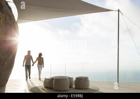 Giovane tenendo le mani sul moderno balcone Foto Stock