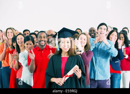 La folla battendo le mani dietro felice laureato Foto Stock