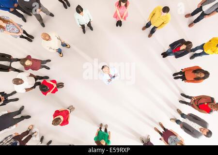 La folla intorno all imprenditore con le braccia incrociate Foto Stock