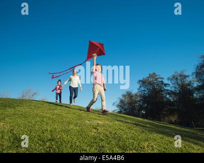 Madre e bambini aquilone volante in posizione di parcheggio Foto Stock