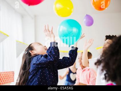 Bambini che giocano con palloncini colorati a parte Foto Stock