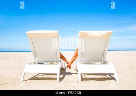 Giovane holding hands in sedie a sdraio sulla spiaggia Foto Stock