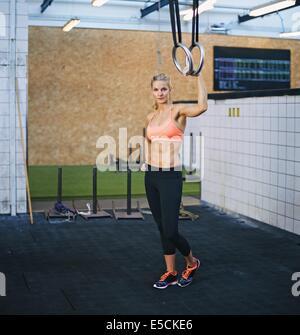 Attraente modello femminile di contenimento degli anelli ginnasta. Giovane donna caucasica in palestra con anelli. Foto Stock