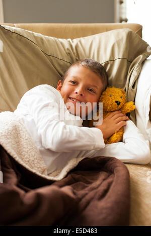 Ragazzo in appoggio sul letto con teddy Foto Stock