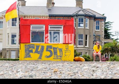 Vita femminile guardia accanto a una capanna con graffiti a Bray Strand, County Wicklow Irlanda Foto Stock