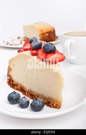 Fetta di Cheesecake con frutti di bosco e una tazza di caffè Foto Stock