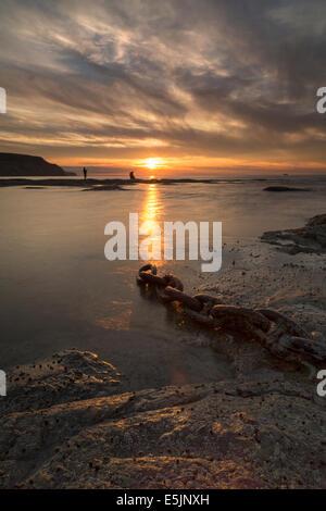 Due giovani uomini la pesca sulla riva a Staithes sulla North Yorkshire coast al tramonto a metà estate. Foto Stock