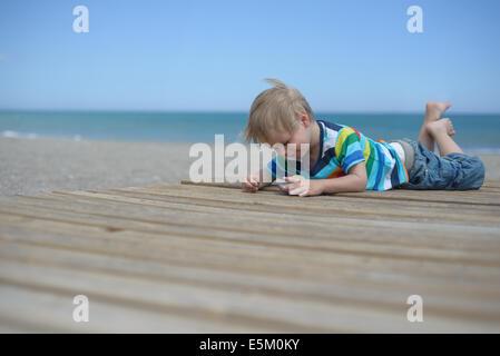 Ragazzo che stabilisce su una passerella in legno sulla spiaggia Foto Stock