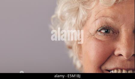 Parte di senior donna faccia con focus su occhi grigi. Vecchia donna faccia close-up con copia spazio su contro uno sfondo grigio. Foto Stock