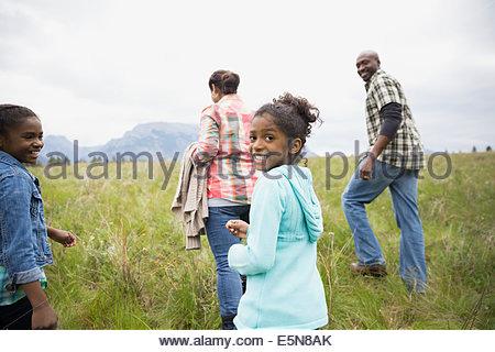 Famiglia passeggiate nel campo erboso Foto Stock