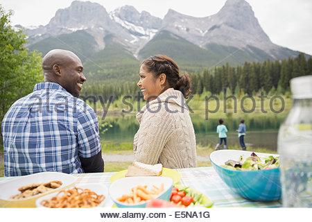 Giovane seduto al tavolo da picnic vicino al lago Foto Stock