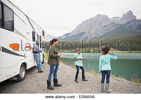 Famiglia permanente al lago vicino a RV Foto Stock