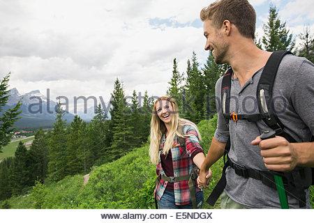Coppia sorridente escursioni vicino alle montagne Foto Stock