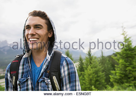 Uomo sorridente in felpa con cappuccio vicino alle montagne Foto Stock