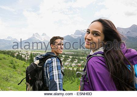 Coppia con zaini trekking vicino alle montagne Foto Stock