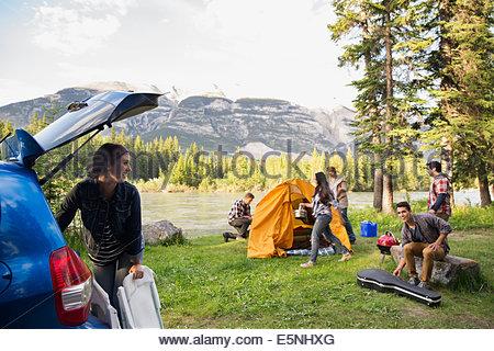 Amici assemblaggio di tenda al campeggio vicino alle montagne Foto Stock