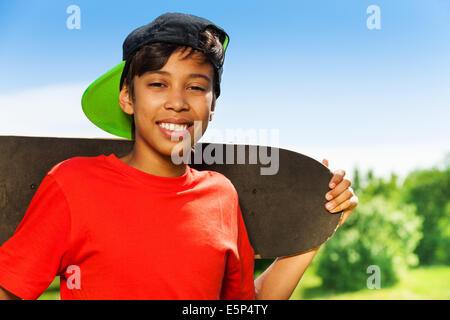 Cool boy nel cappuccio e con ritratto di skateboard Foto Stock