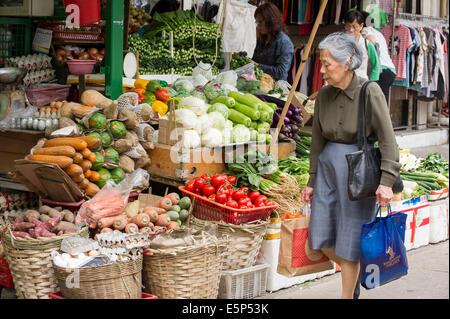 Donna passando da un Hong Kong street market stand vegetali. Foto Stock