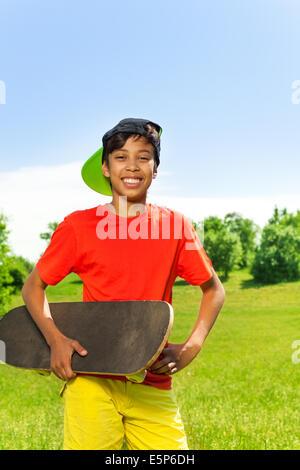 Felice ragazzo nel cappuccio e con ritratto di skateboard Foto Stock
