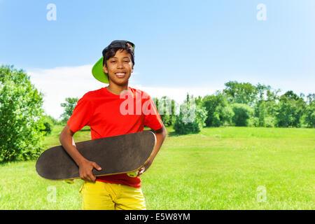 Ragazzo sorridente nel cappuccio e con ritratto di skateboard Foto Stock