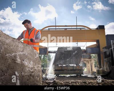 Lavoratore di cava di roccia di misura nella parte anteriore della sega di pietra