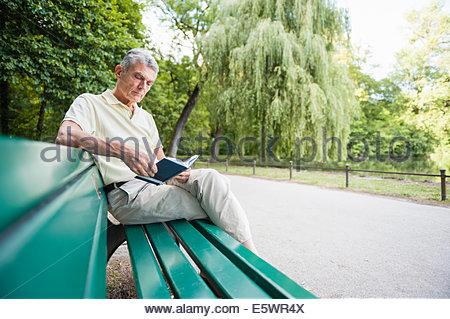 Senior adulto uomo seduto su banco del libro di lettura Foto Stock