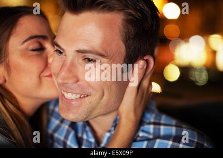 La condivisione di coppia bacio sulla guancia in taxi della città di notte Foto Stock
