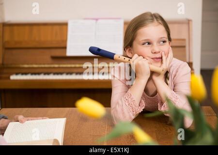 Annoiato distratto ragazza con strumento registratore in sala da pranzo Foto Stock