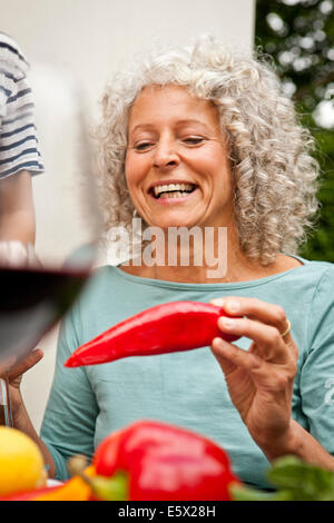 Donna matura tenendo un peperone rosso Foto Stock