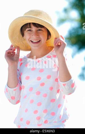 Ritratto di dieci anno vecchia ragazza tenendo premuto sul cappello di paglia Foto Stock