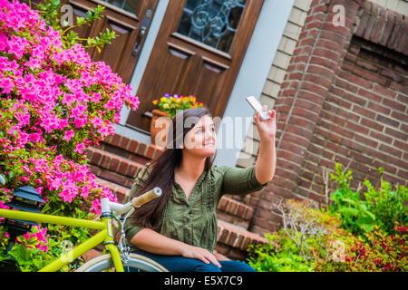 Giovane donna prendendo selfie sullo smartphone sui gradini di una casa Foto Stock